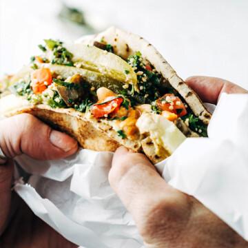 A closeup up of a man's hands holding a pita sandwich
