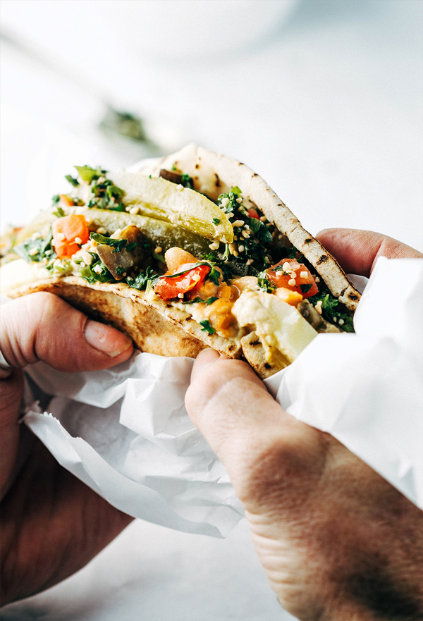 close up image of man's hands holding a large vegan Sabich sandwich