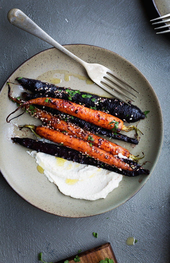 A overhead image of a serve of miso maple roasted carrots sitting on an olive coloured plate with a dollop of cashew cream and parsley sprinkles