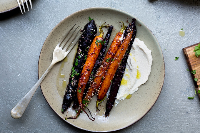 A horizontal overhead image of a serve of miso maple roasted carrots sitting on an olive coloured plate with a dollop of cashew cream and parsley sprinkles