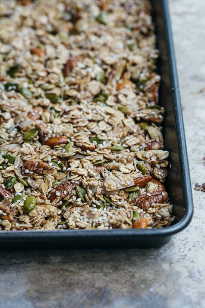 Close-up image of the chunky sesame granola pressed in to the tray before baking. This is a process shot before the granola is cooked to show how muck to push the mixture in to the pan.