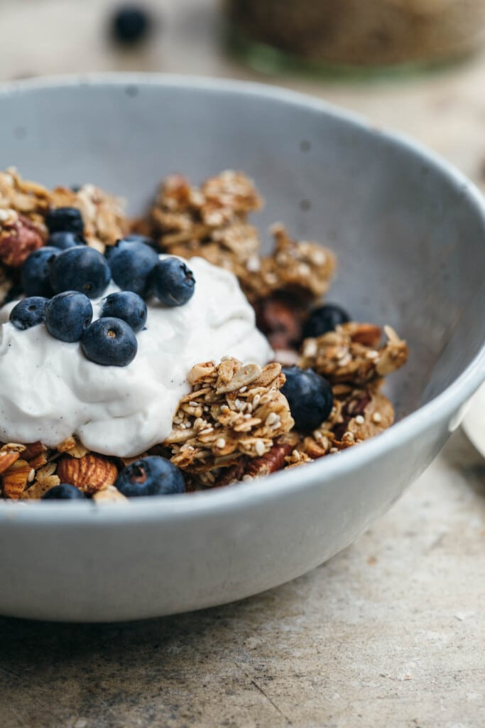 Close up image of chunky sesame granola in a white bowl with coconut yoghurt and blueberries