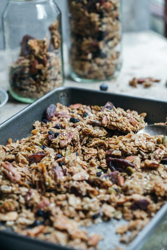 A mid-shot of the tray of freshly baked granola after it has been broken in to chunks. Two jars of granola are in the background.