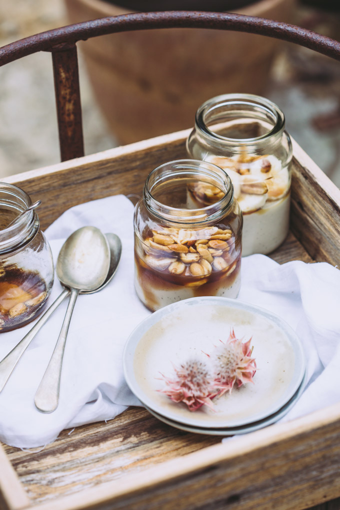 A rustic wooden box resting on a swing seat with three jars of vegan panna cotta, textured napkins and spoons.