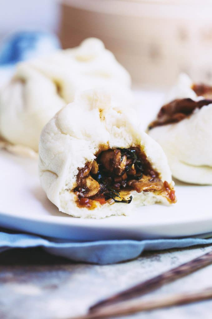 A close-up image of a vegan bao bun with a bite taken out of it on a white plate