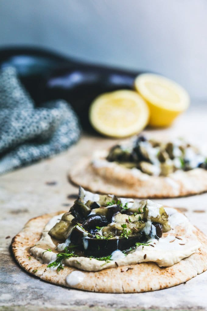 front on image of a spiced eggplant pita with hummus on a concrete bench with another pita in the background. Cut lemon and a blue cloth sit off the left rear of the image.