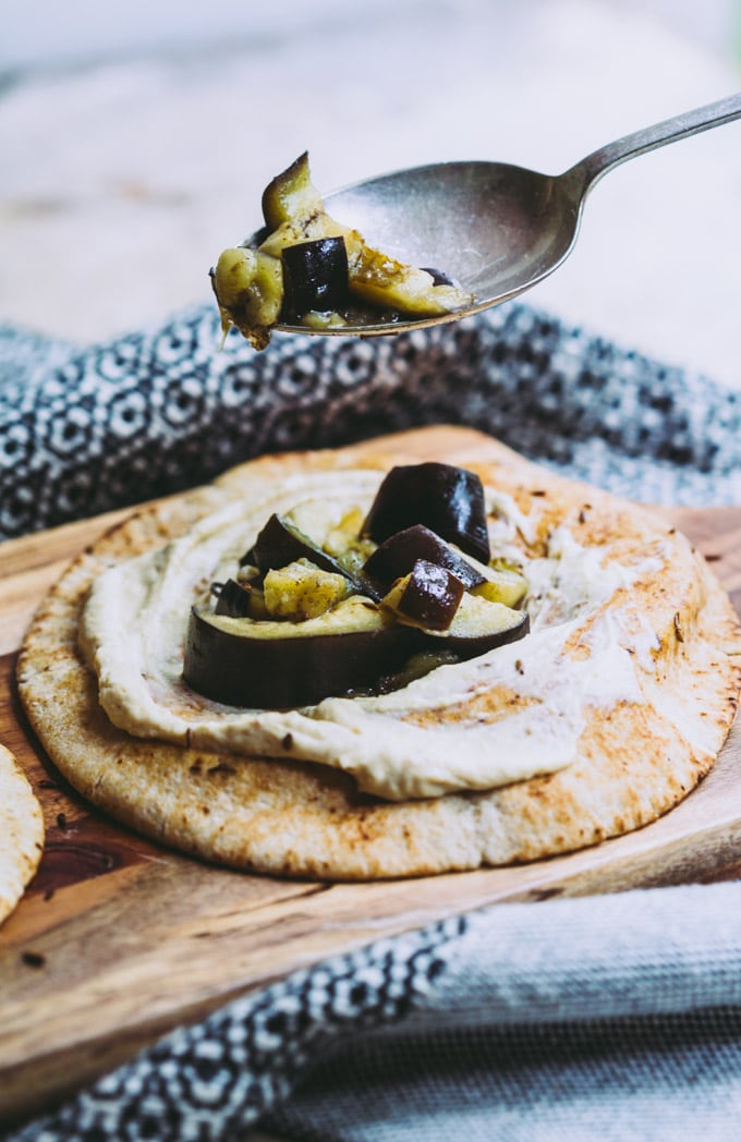 A close up image of the steamed eggplant being spooned on to a pita bread with hummus