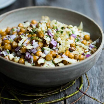 A bowl of chickpea salad on a wooden bench