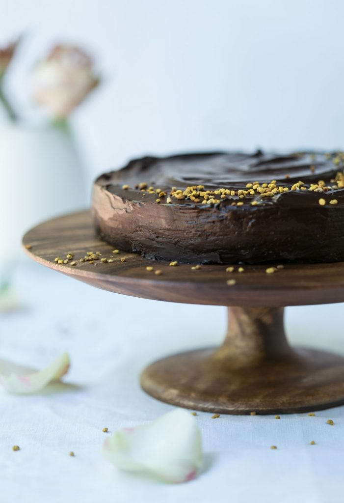 Raw chocolate cake on a wooden cake stand