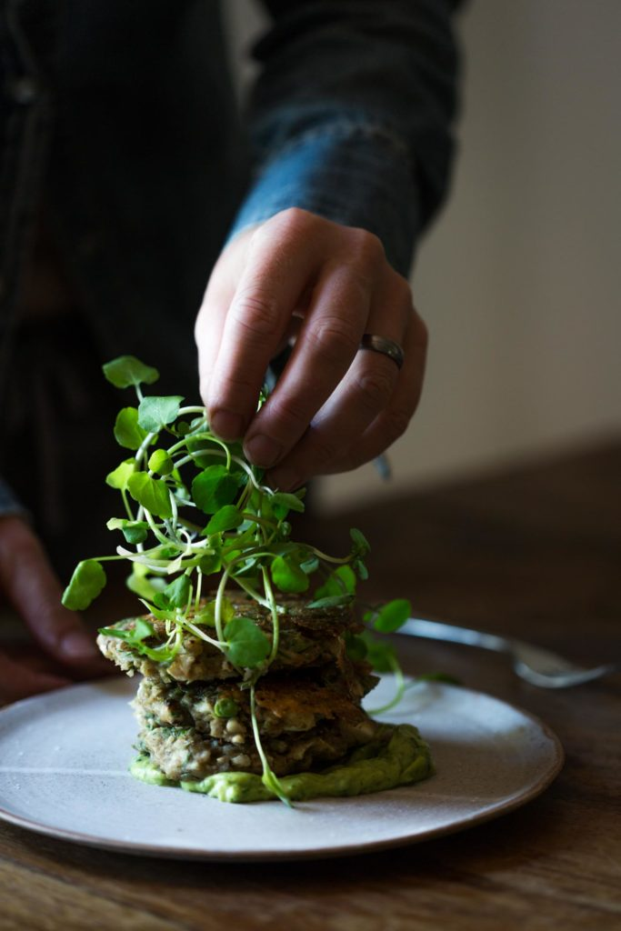 A close up of a woman adding fresh greens to a stack of fritters
