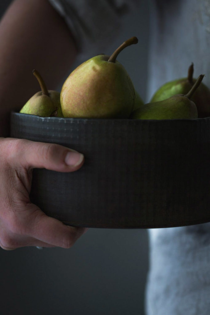 close-up image of a woman holding a vintage container full of ripe pears