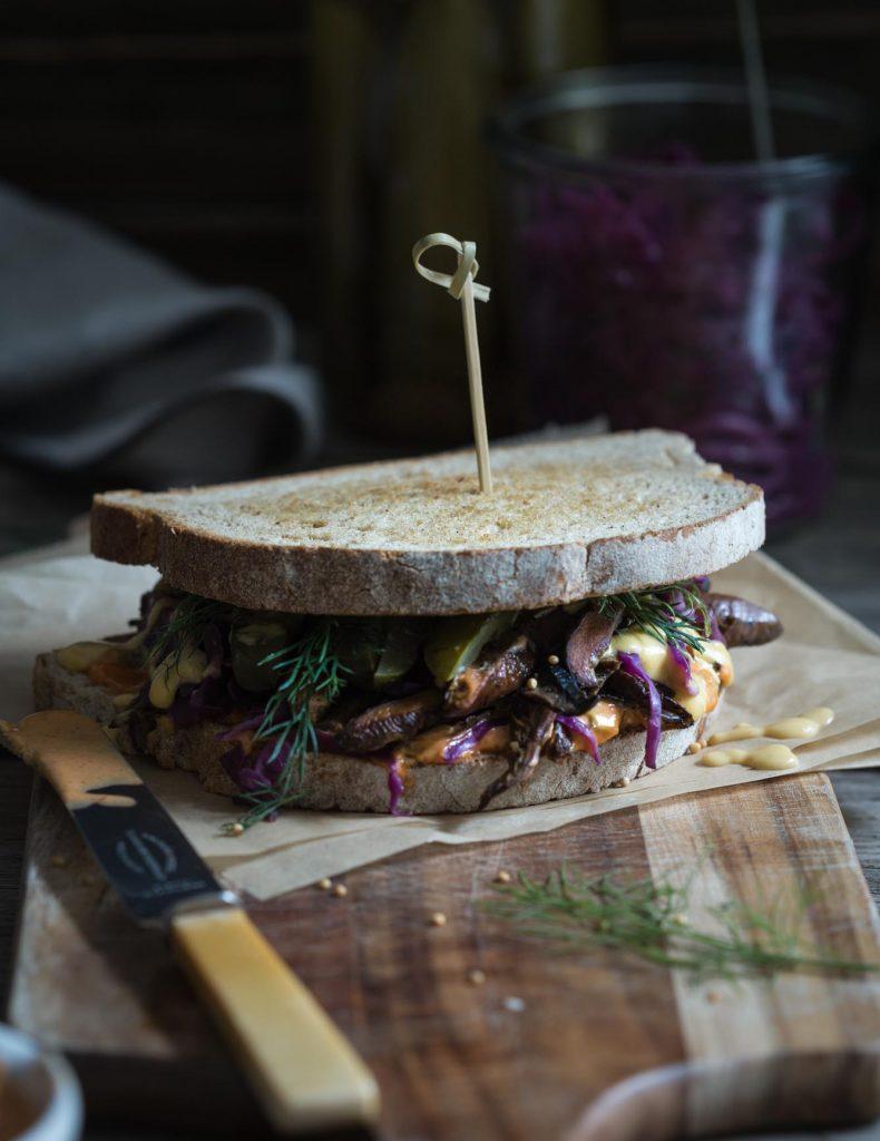 Vegan Mushroom Reuben Sandwich sitting on a cutting board