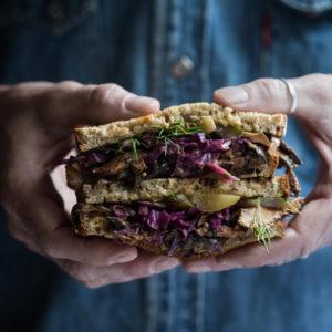 Close up of man holding reuben sandwich