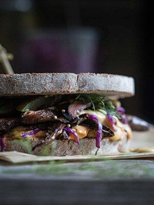 A close up of a Reuben sandwich on a cutting board