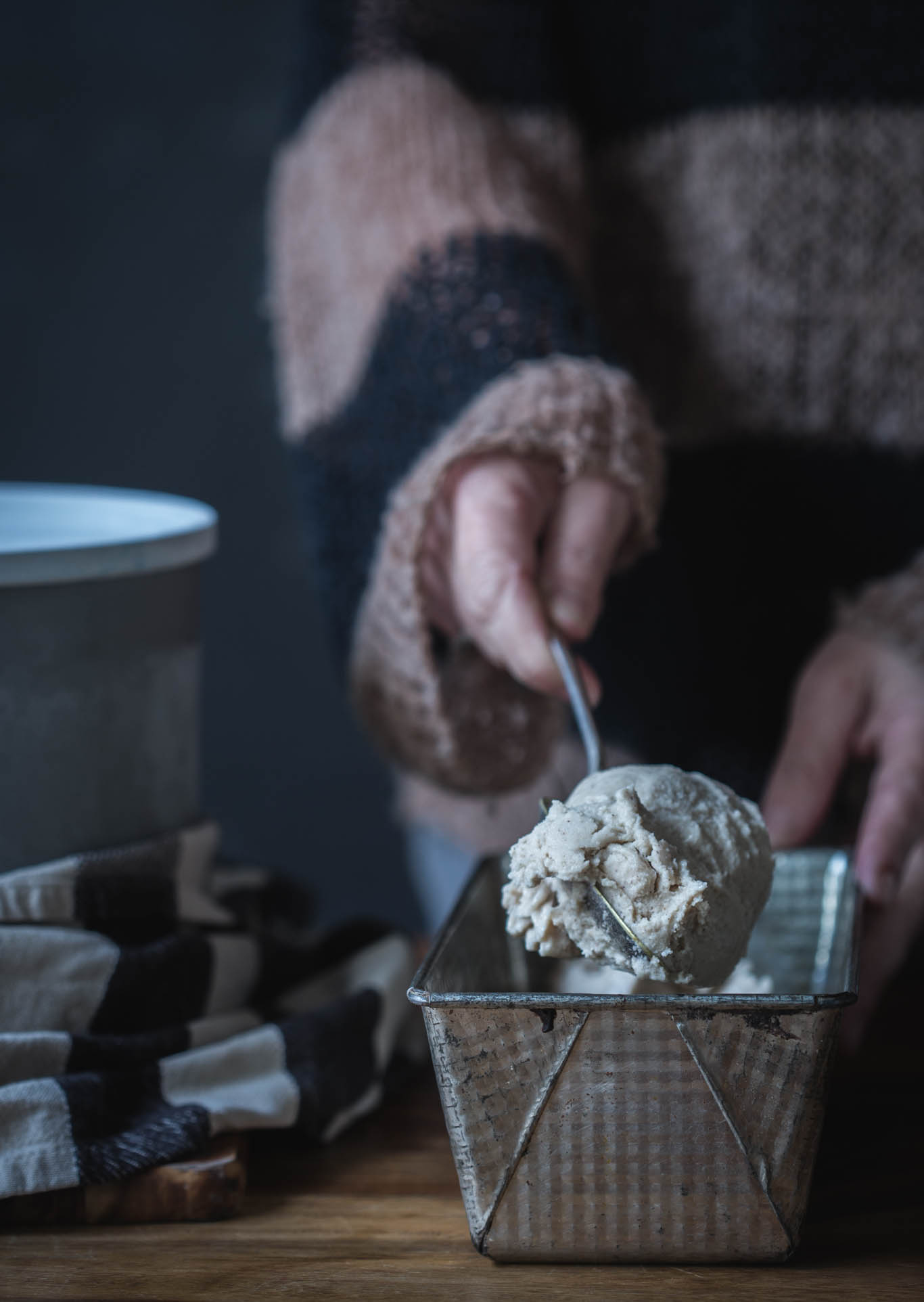 A woman scooping a big scoop of ice cream from a vintage metal loaf tin.