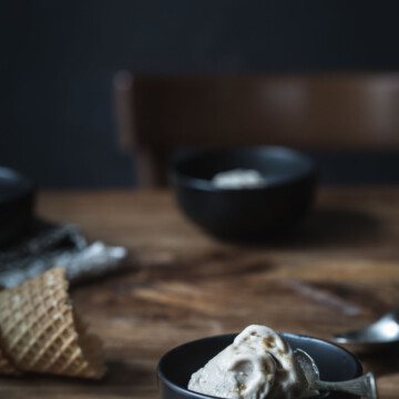 Gingerbread ice cream in small black bowls with waffle cones nearby.