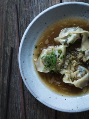 An overhead image of bowl of soup with wontons.