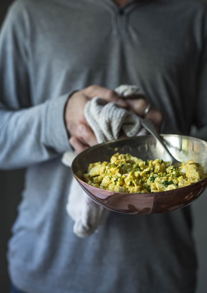 A man holding a copper pan containing soft scrambled tofu