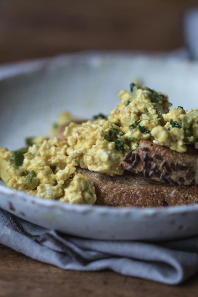 Close up of plate of scrambled tofu on toast in white bowl