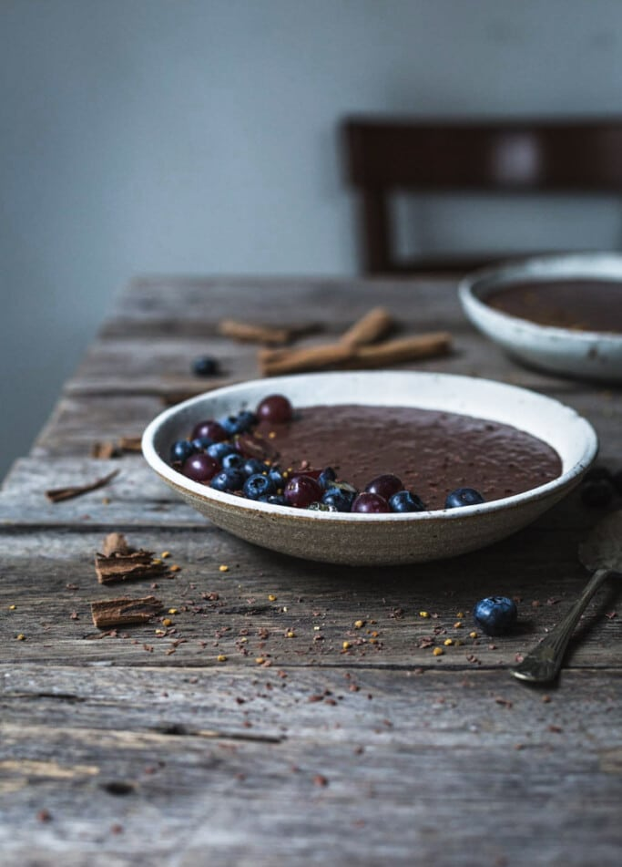 A rustic wooden table set for breakfast with a clay bowl of Mexican-inspired chocolate chia pudding with blueberries and purple grapes in the foreground and another in the background