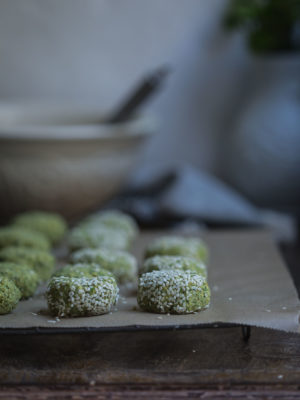 Rows of green falafel on a tray before cooking