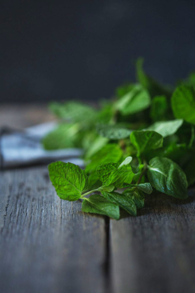 Close up image of freshly picked mint on a rustic wooden bench