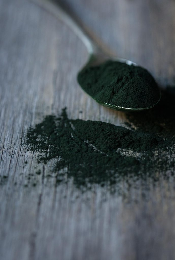 A close up image of a spoon of dark green spirulina powder to show ingredient