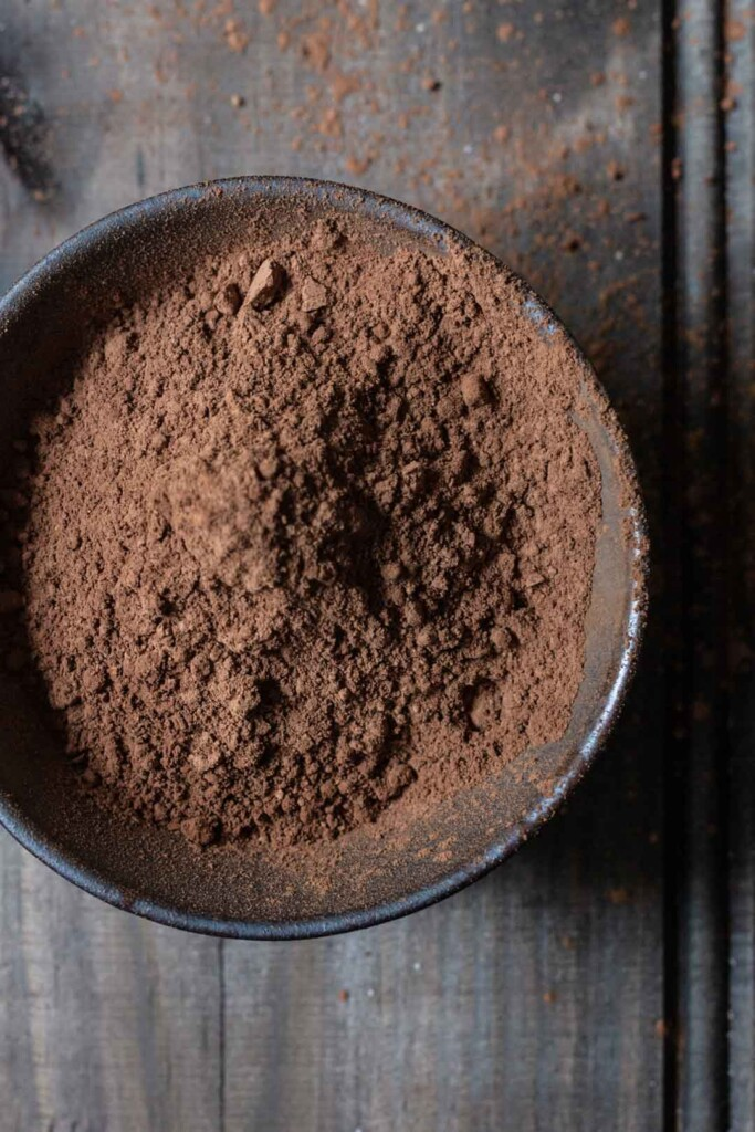 close-up process image of a bowl of raw cocoa measured to go in to the vegan chocolate beetroot cakes