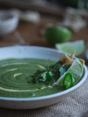 A bowl of broccoli and jalapeño soup in a white bowl.