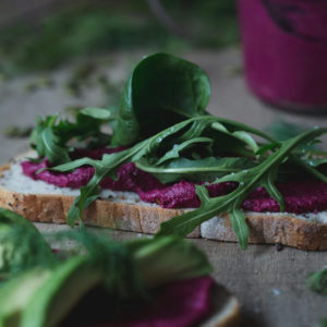 A close up image of a slice of bread topped with beetroot hummus and greens.