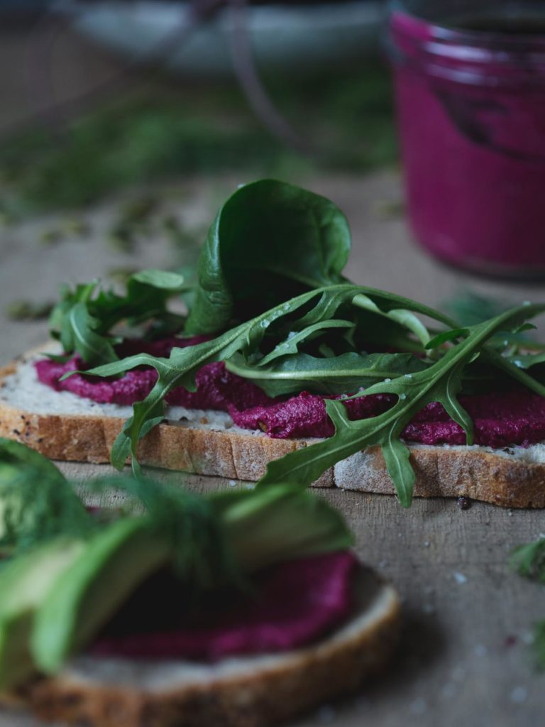 45 degree angled shot of a slices of rustic bread smeared with beet butter and fresh green rocket. Jar of beet butter in the background.
