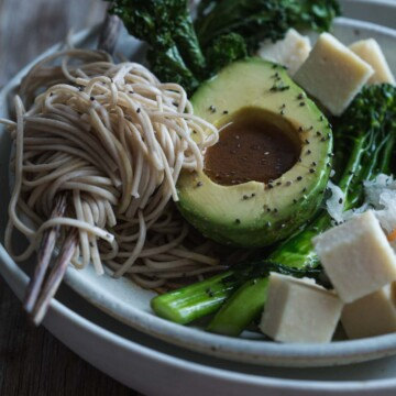 A close up image of a salad bowl with chickpea tofu and noodles.
