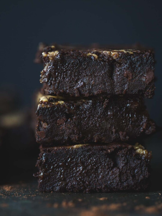 A front on image of a stack of caramel tahini black bean brownie squares stacked on a rustic metal tray