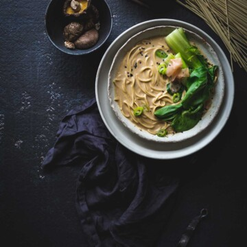 An overhead image of a bowl of noodles with ingredients on a dark background.