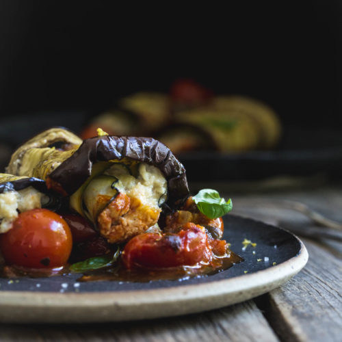 A close up image of stuffed eggplant rolls with tomatoes on a black plate.