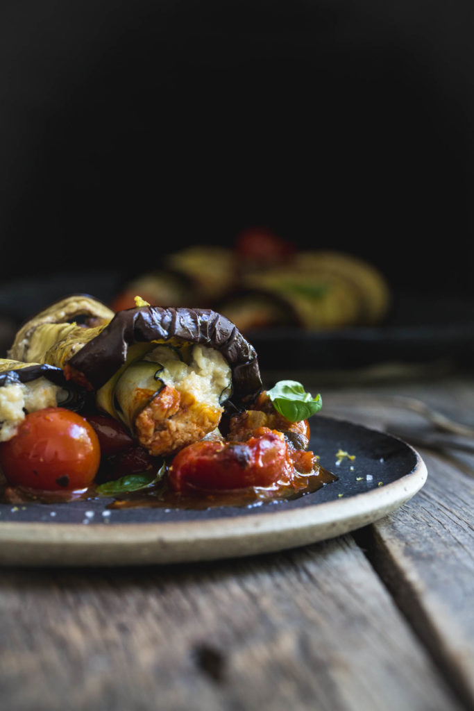 Close up of vegan eggplant involtini on a dark plate