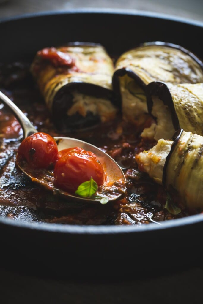 Skillet of half-eaten vegan eggplant involtini with a serving spoon