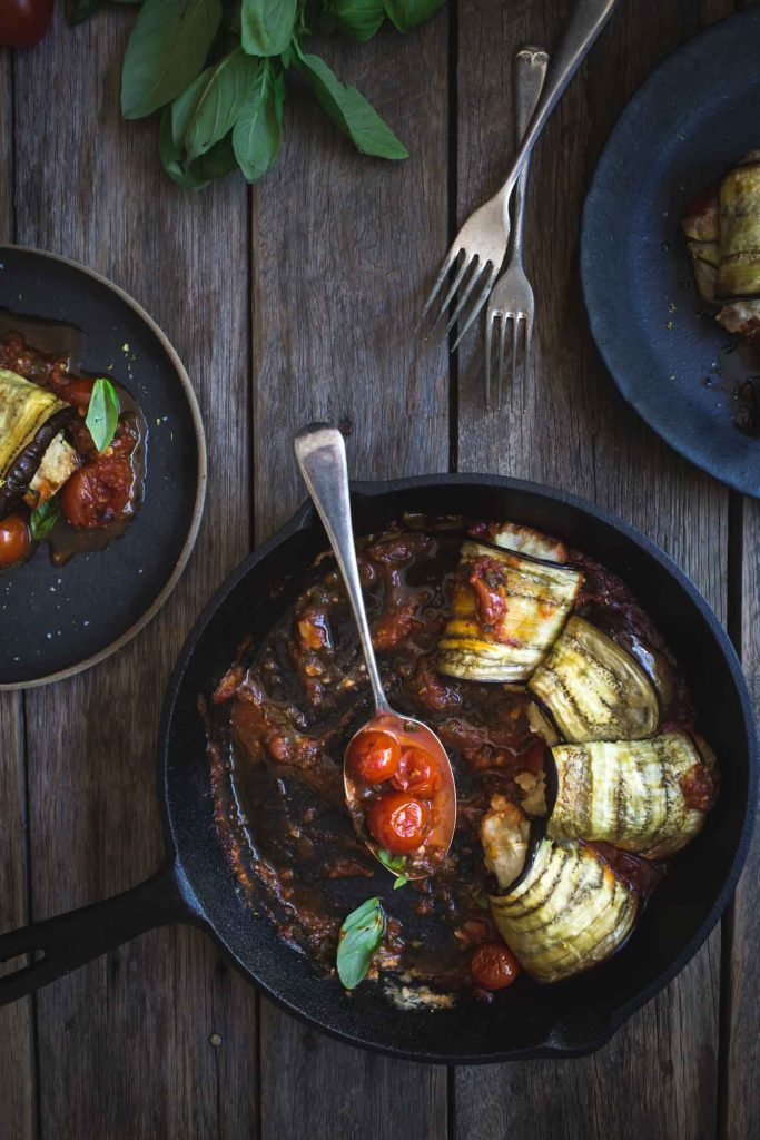 Flat lay image of servings of eggplant involtini and a serving skillet
