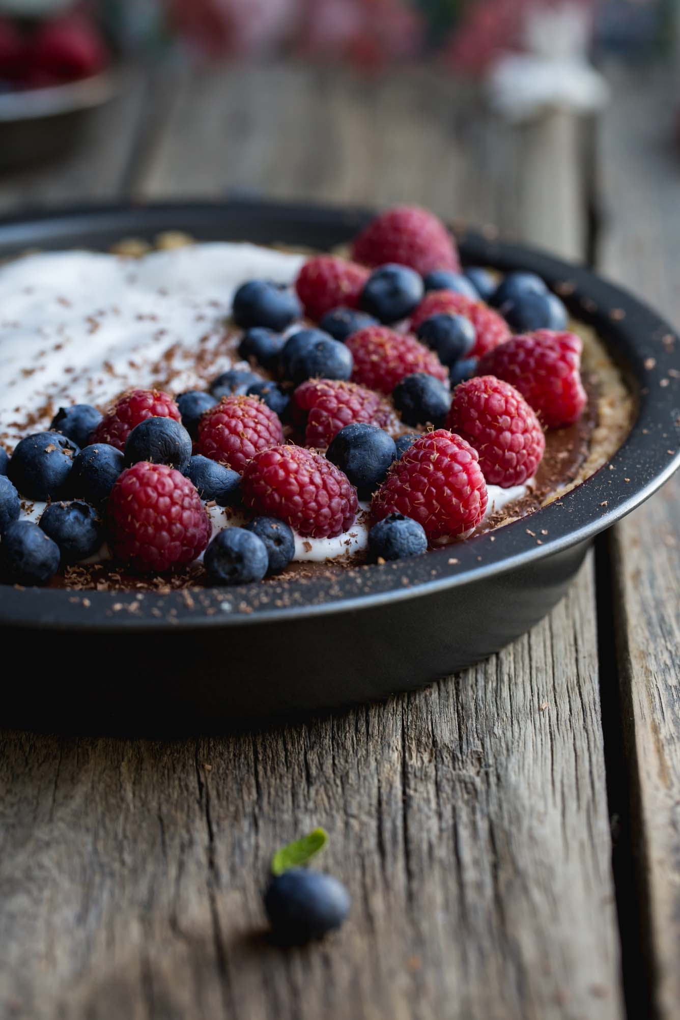 A close up image of a chocolate pie with cream and berries on a wooden bench.