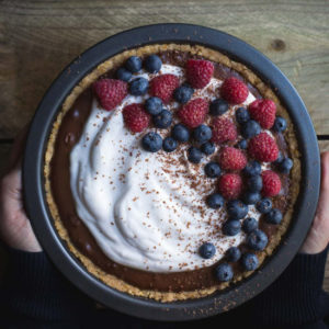 An overhead image of a woman holding a chocolate pie with cream and berries.