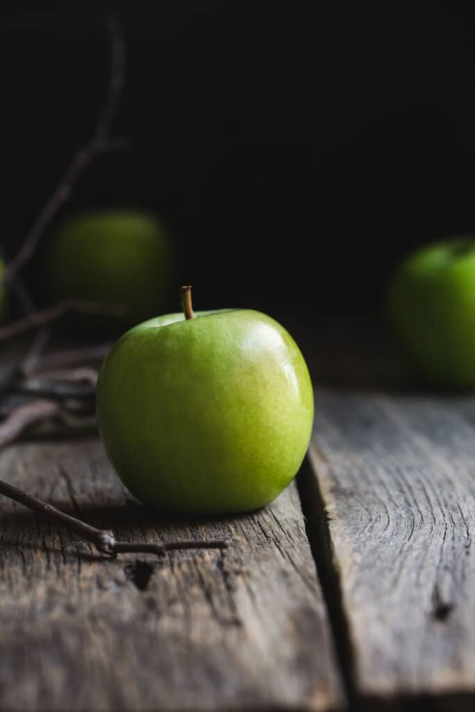 Green Granny Smith apples sitting on a rustic wooden bench before being made in to Halloween toffee apples. A pile of small branches sit off to the side.