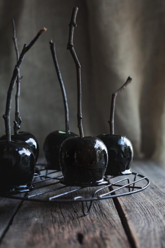 A front on image of 5 Halloween toffee apples with branch handles sitting on a round wire tray