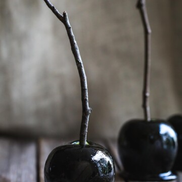 A close up of black toffee apples with twig handles on brown parchment.