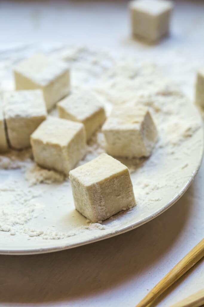 A close up image of the uncooked tofu rolled in the flour before being fried.
