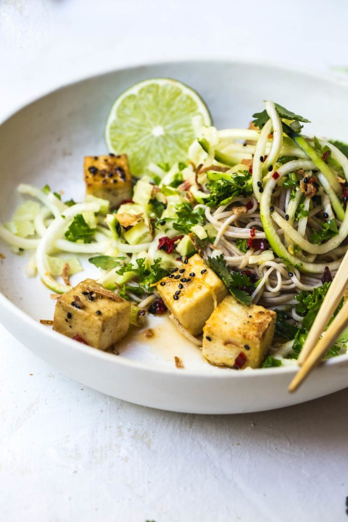 A close-up image of the crispy tofu and lemongrass in a white bowl with zucchini and soba noodles and a chopsticks off to the side.
