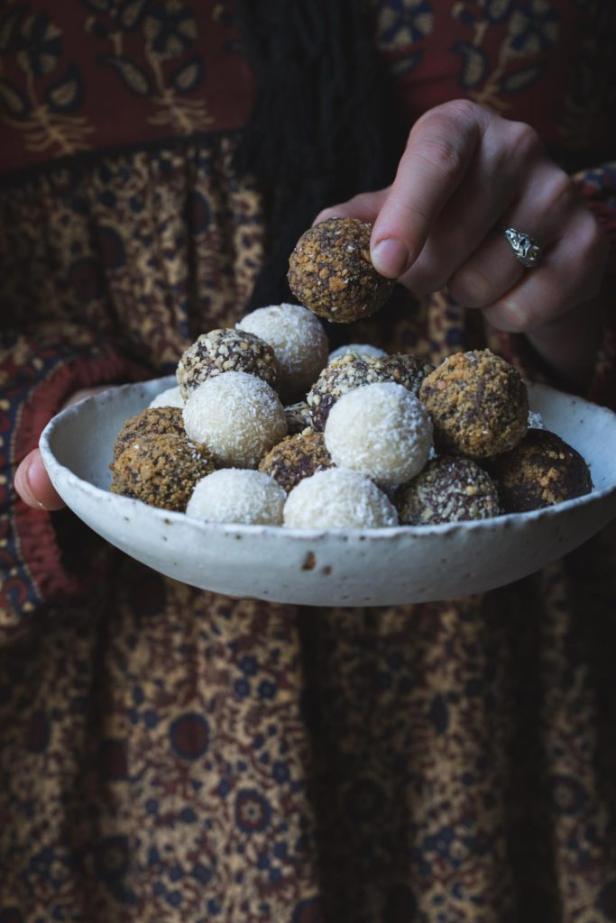 woman holding a bowl of vegan truffles