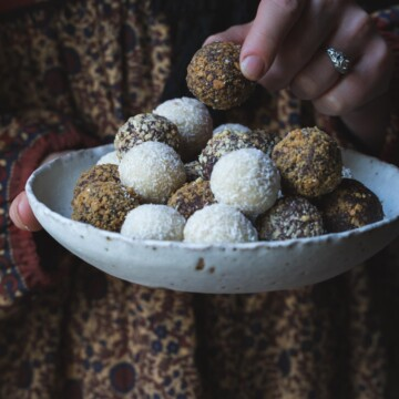 A woman's hand picking up a chocolate truffle from a bowl.