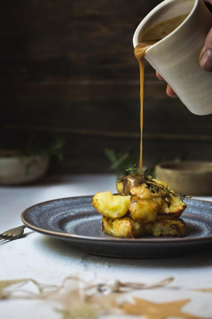 Front on image of a man's hand pouring vegan gravy over a stack of smashed potatoes.