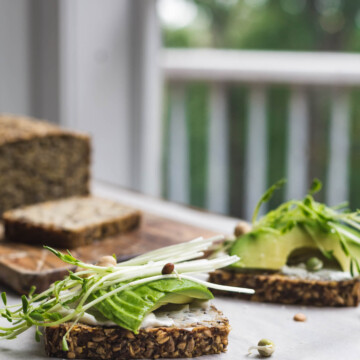 A sliced loaf of seeded bread with some slices topped with avocado and greens.