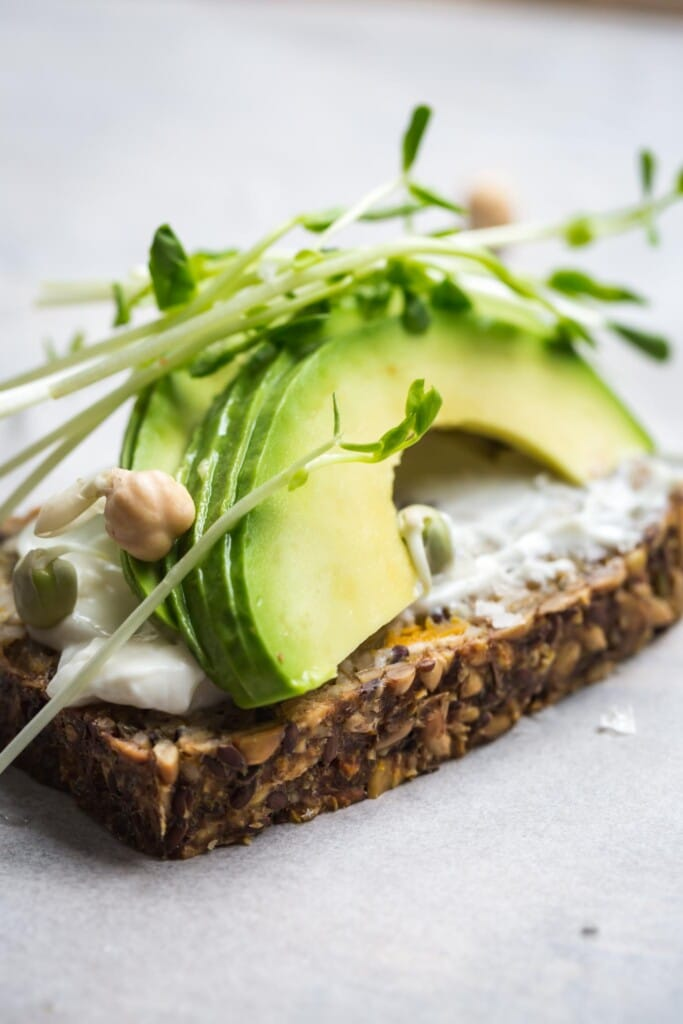 A close up image of seeded pumpkin toast topped with mayonnaise and sliced avocado